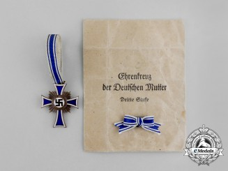 A Bronze Grade  Cross of Honour of the German Mother in its Packet of Issue by Gebrüder Schmidt