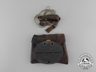 A First War German Identification Tag with Original Leather Pouch and String Necklace