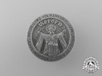 A 1935 Munich Grocery and Luxury Foodstuffs Reichs Exhibition Badge by Willy Annetsberger