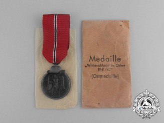 A Second War German Eastern Winter Campaign Medal in its Packet of Issue; by Deschler & Sohn