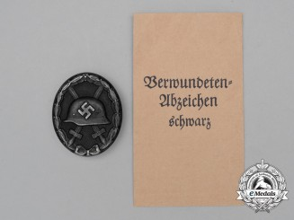 A Second War German Black Grade Wound Badge in its Packet of Issue by Ludwig Bertsch