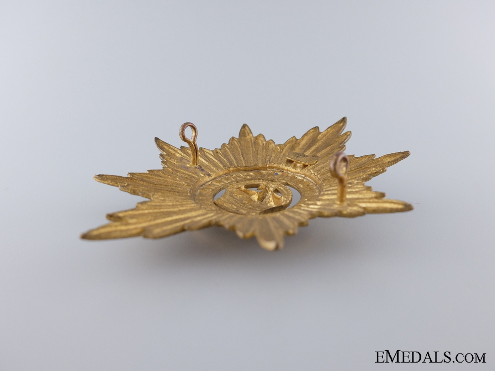 A WWII Royal Military College Pith Helmet Cap Badge